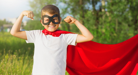 cape: Superhero kid showing his muscles over nature background Stock Photo