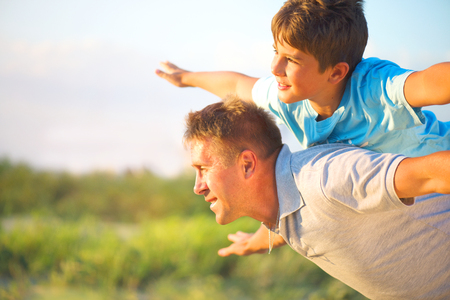 happy holidays: Happy father and son having fun over beautiful sky outdoors