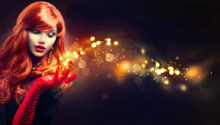spark: Beauty glamour woman with golden magic sparks in her hand Stock Photo