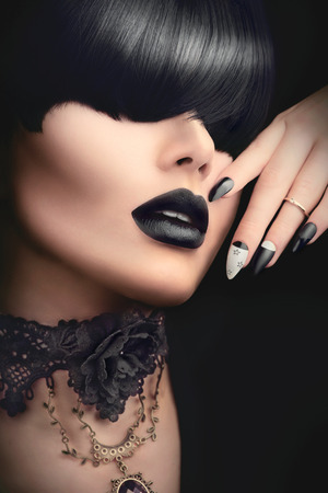 Fashion model girl with black gothic hairstyle, makeup, manicure and accessories