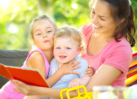 Happy mother reading book to her little children in sunny park Stock Photo