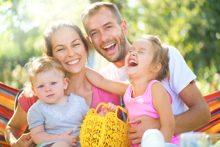 Happy joyful young family with little children outdoors Stock Photo