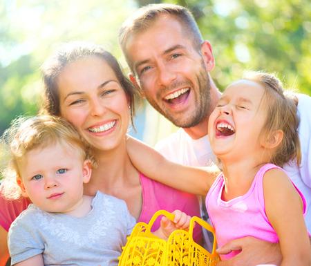 Счастливый радостное молодая семья с маленькими детьми на открытом воздухе