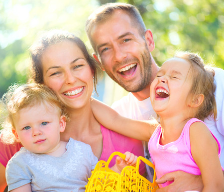 Happy joyful young family with little children outdoors photo
