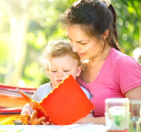Happy mother reading a book to her little baby in sunny park