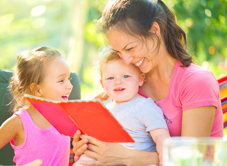 Happy mother reading a book to her children in sunny park photo