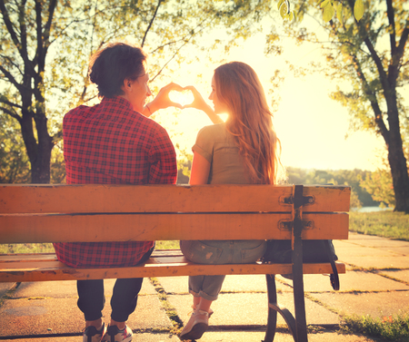 lovers park: Happy young couple sitting on the bench in sunny park and making heart gesture together
