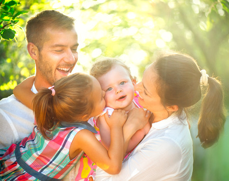 Happy joyful young family with children having fun outdoors in orchard garden photo
