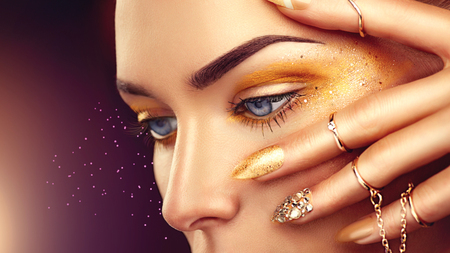 Beauty fashion woman with golden makeup, gold accessories and nails