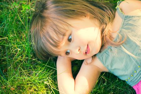 Cute smiling little girl lying on green grass
