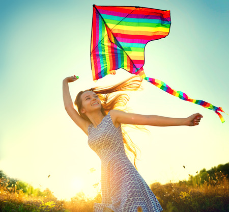 Beauty girl in short dress running with kite on the field Stock Photo