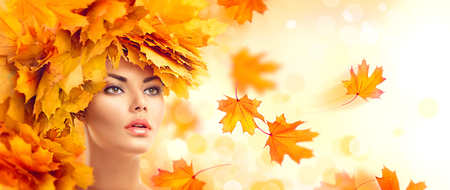 fashion: Autumn woman. Fall. Beauty model girl with autumn bright leaves hairstyle