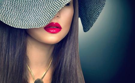 Красивая сексуальная брюнетка женщина с красными губами в современной черной шляпе