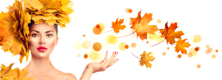 space for text: Model girl with autumn bright leaves hairstyle showing empty copy space on open hand palm for text