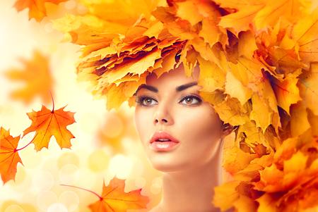 Mulher do outono. Cair. Menina modelo da beleza com amarelo brilhante deixa penteado