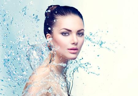 Beauty spa vrouw onder scheutje water over blauwe achtergrond