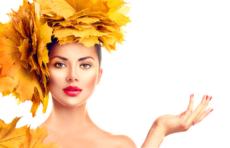 palm: Fall. Beauty model girl with autumn bright leaves hairstyle. Girl showing empty copy space on open hand palm