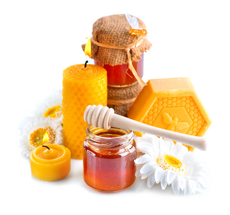 Honey, natural wax and wax candles isolated on white. Spa and alternative medicine