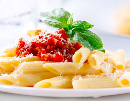 Pasta Penne with Bolognese sauce, Parmesan cheese and Basil Stock Photo