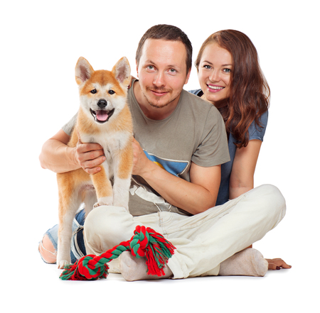 akita: Smiling couple with dog sitting together over white background. Cute little Akita Inu puppy