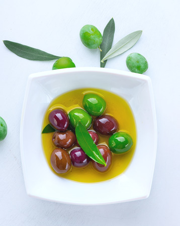 Olives and olive oil. Mixed marinated olives in ceramic bowl
