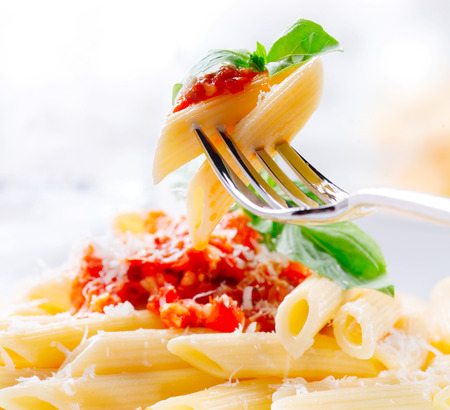 Pasta Penne with Bolognese sauce, Parmesan cheese and Basil on a Fork
