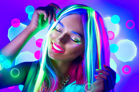 Young woman dancing in neon light. Beauty model girl with fluorescent make-up