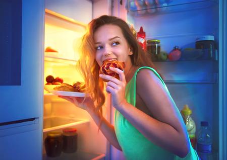 anochecer: adolescente hermosa que toma los alimentos del refrigerador durante la noche