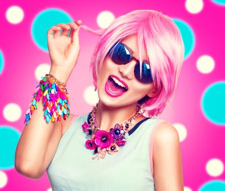 Krása dospívající modelu dívka s růžovými vlasy, módní barevnými doplňky a sluneční brýle