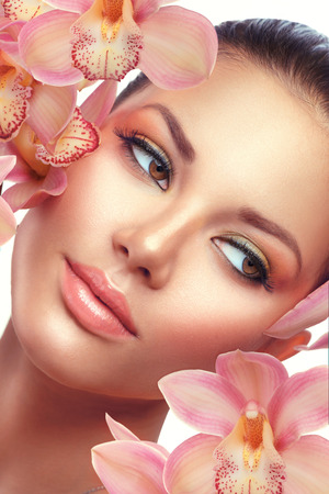 Spa. Beautiful brunette model girl portrait with orchid flowers