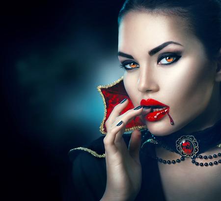 美容: 萬聖節肖像。美容性感的吸血鬼女子在她的嘴裡鮮血淋漓