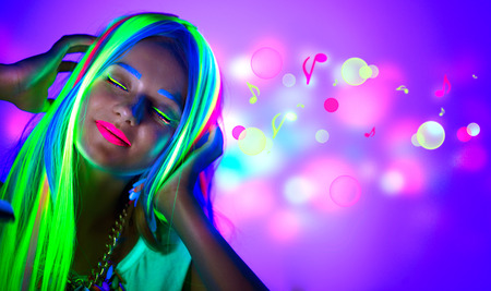 lips glow: Beautiful young woman in neon light. Disco girl with fluorescent make-up Stock Photo