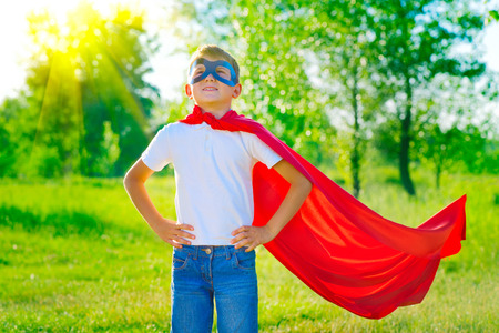 strong: Superhero little boy over nature green blurred background