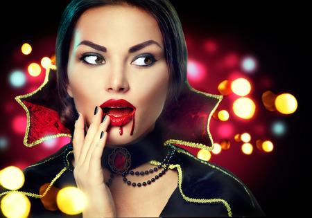 satanas: retrato de Halloween. Mujer atractiva de la belleza del vampiro con gotas de sangre en la boca