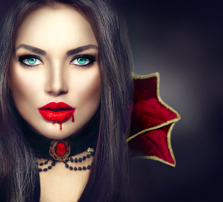 Halloween vampire woman portrait. Sexy vampire girl with dripping blood on her mouth
