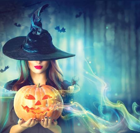 Bruja con una calabaza de Halloween en un bosque oscuro