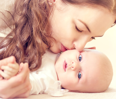 Happy mother kissing her newborn baby photo