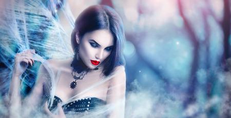 ファンタジー ハロウィン女性の肖像画。美しさセクシーな吸血鬼ポーズ、クモの巣を着て