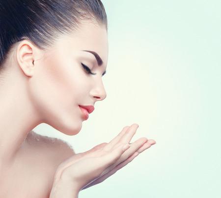 Krása lázeňské žena s dokonalou pleť ukazuje prázdné kopie prostor na otevřenou ruku dlaní