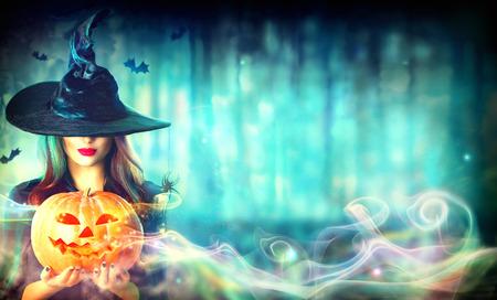 Sexy heks met een Halloween pompoen Jack-o-lantern in een donker bos Stockfoto