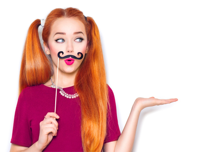 Funny teenage girl with paper mustache on stick showing empty copy space