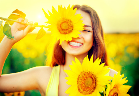 Beauty joyful teenage girl with sunflower enjoying nature