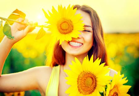 Beauty vrolijke tiener met zonnebloem genieten van de natuur