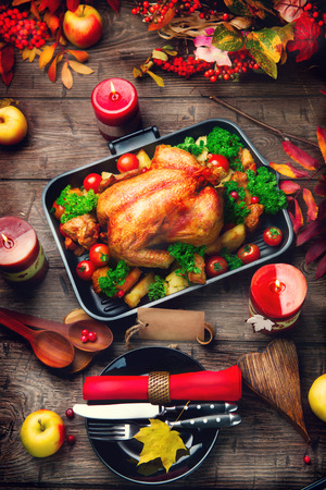 Thanksgiving table served with turkey, decorated with bright autumn leaves Stockfoto