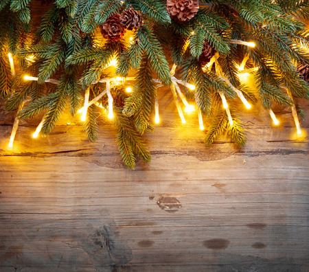aged: Christmas fir tree with Christmas lights over wooden background Stock Photo