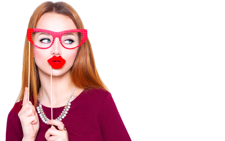 fake smile: Funny young woman holding glasses and red lips on stick