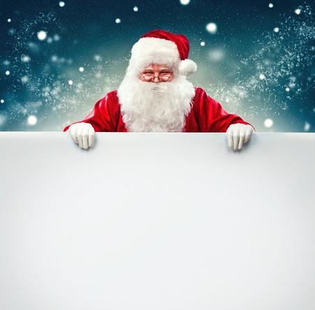 Santa Claus drží prázdné reklamní banner pozadí s kopií prostor