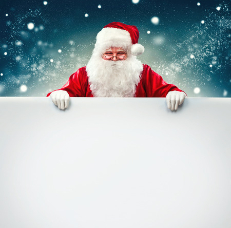 feliz navidad: Santa Claus holding blank advertisement banner background with copy space Stock Photo