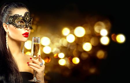 Modelo de mulher sexy com vidro do champanhe que desgasta a máscara mascarada Venetian