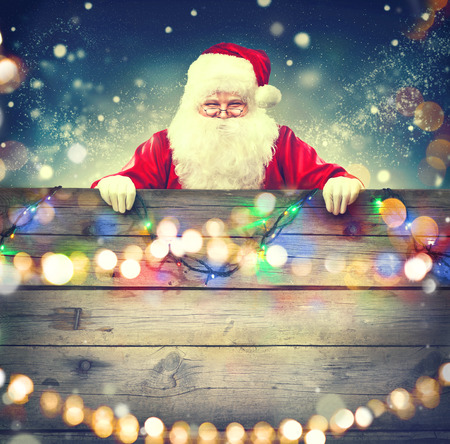 Happy Santa Claus holding wooden banner background. Christmas theme